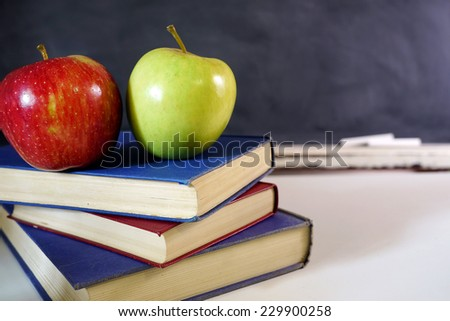 two apples on books in classroom