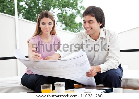 Two architect working on blueprints at work. - stock photo