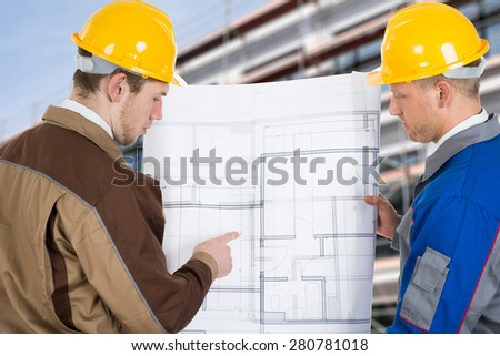 Two Architects At Construction Site Discussing Blueprint