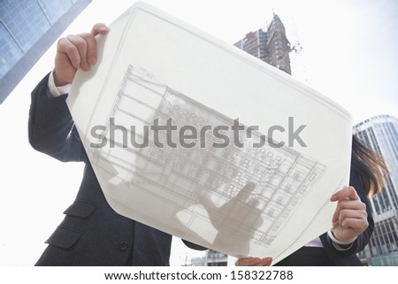 Two architects looking at a blueprint at a construction site