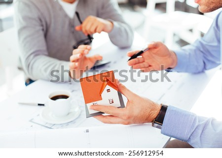 Two architects sitting at a desk and discussing construction issues - stock photo
