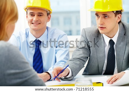 Two architects talking to their colleagues - stock photo