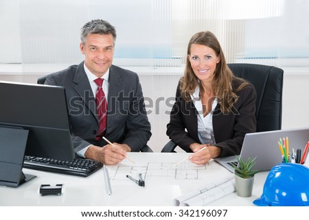 Two Architects Together Discussing Blueprint At Desk In Office
