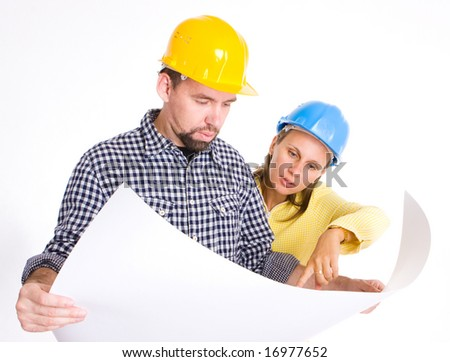 two architects wearing hardhats looking to the blueprint