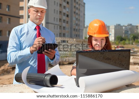 Two architects wearing protective helmet works in front of building site