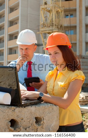 Two architects wearing protective helmet works in front of building site - stock photo