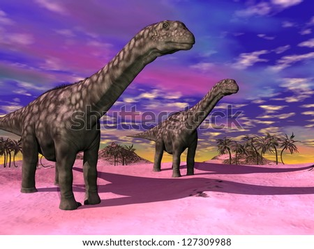 Two argentinosaurus dinausors in a prehistoric wild landscape and colorful sky - stock photo