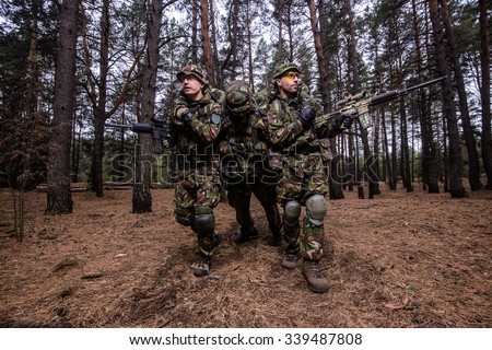 Two armed men in military uniform evacuate wounded soldier from the battlefield/Evacuation of wounded soldier in forest - stock photo