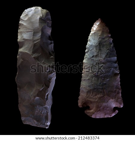 Two Arrowheads, one unfinished and one complete, isolated on black. - stock photo