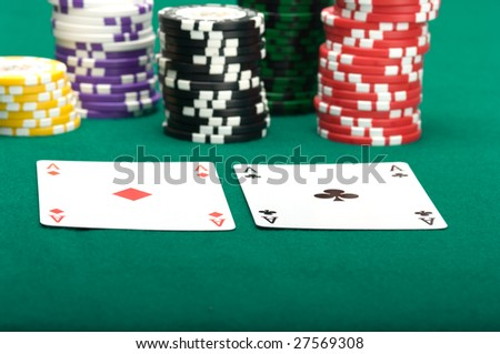 Two ases and piles of counters on green cloth.
