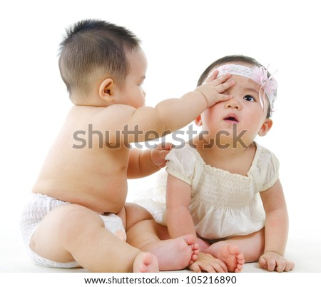 Two Asian babies sitting on white background - stock photo