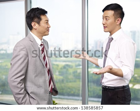 two asian business executives standing and talking by the windows in office.