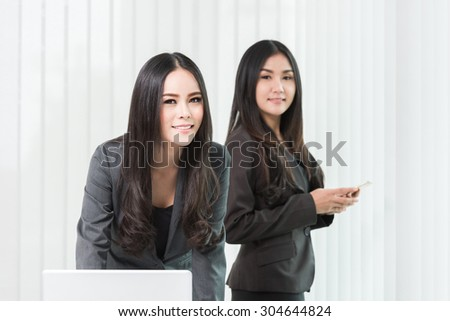 Two asian business women having a meeting with laptop in modern office - stock photo