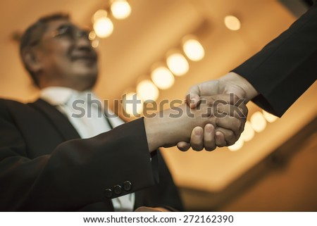 Two Asian businessman shaking hands - stock photo
