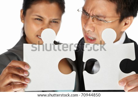 Two Asian businesspeople trying to connect the puzzle pieces - stock photo