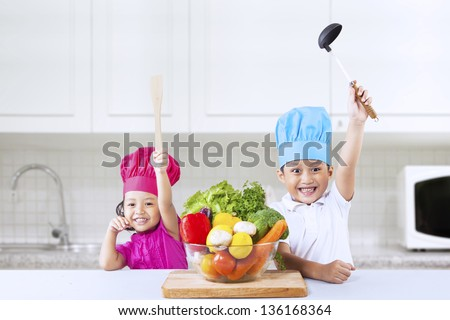 Two Asian cheerful chef kids in kitchen - stock photo