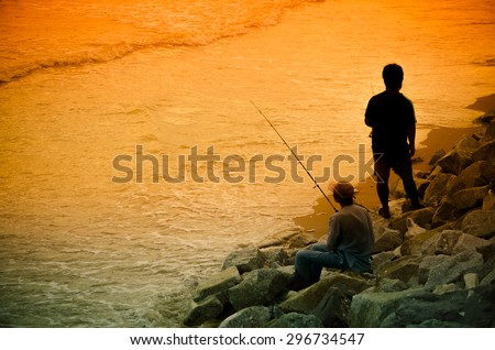 Two Asian Fisherman fishes on the lake. Silhouette at sunset