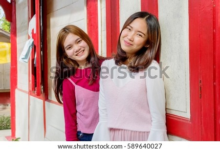 Two Asian Girls In Pink Vintage Clothes Are Having Fun Time At The Local Train Station