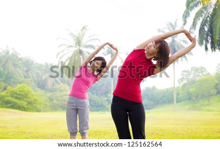 Two Asian girls stretching outdoor green park - stock photo