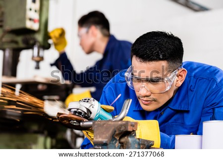 Two Asian industrial workers in metal factory with electrical grinding tool and power drill machine - stock photo
