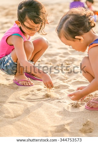 Two Asian Little Girl Enjoy Playing on The White  Beach Sand, Selective Focus on Hand