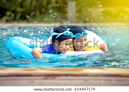 two asian little girls having fun to swim in swimming pool together