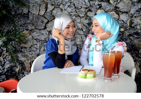 Two asian Muslim young women are chatting while eating - stock photo