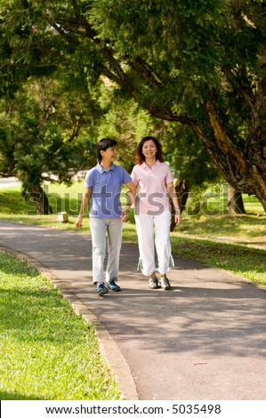 Two Asian women walking in the park talking to each other