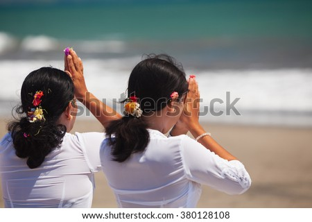 Two asian women with praying hands on ocean beach at ceremony Melasti before Balinese New Year and silence day Nyepi. Holidays, festivals, rituals, art, culture of Indonesian people and Bali island. - stock photo