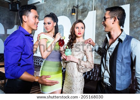 Two Asian young and handsome party people couples drinking cocktails in a luxurious and fancy night club