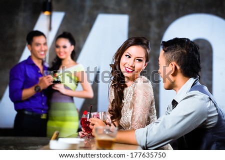 Two Asian young and handsome party people couples flirting and drinking at the bar in luxurious and fancy night club - stock photo