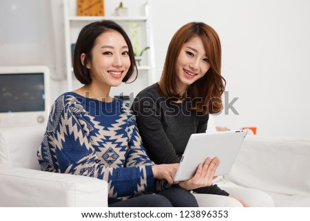 Two Asian young woman using tablet PC.