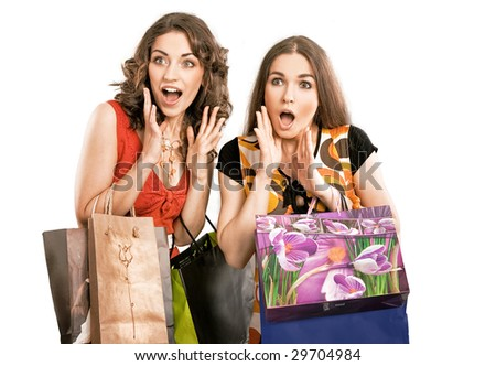 Two astonished girls on shopping trip, isolated on white - stock photo