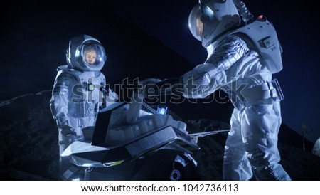 Two Astronauts in Space Suits on an Alien Planet Prepare Space Rover for Surface Exploration Mission. Futuristic Concept about Space Colonization.
