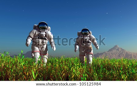 Two astronauts on the green grass. - stock photo