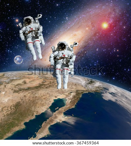 Two astronauts spaceman planet spacewalk outer space walk moon milky way galaxy. Elements of this image furnished by NASA. - stock photo