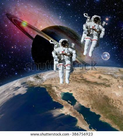 Two astronauts spaceman saturn planet spacewalk outer space walk moon universe. Elements of this image furnished by NASA.
