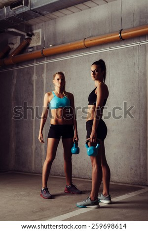 Two athlete women standing with kettlebell in empty garage - stock photo