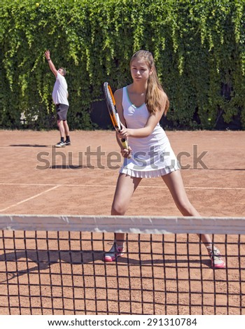 Two athletes on tennis court. Father and daughter starting new game on clay tennis field male serving female stays advanced to net anticipating competitor response - stock photo