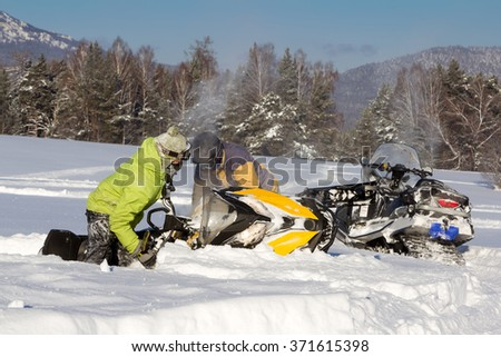 Two athletes pulled out of a snowdrift snowmobile. Walking in the mountains of the Southern Urals.