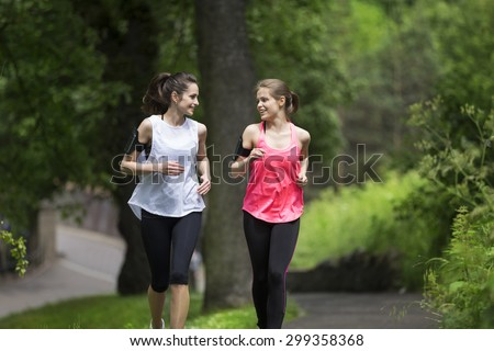 Two athletic woman running outdoors. Action and healthy lifestyle concept. - stock photo