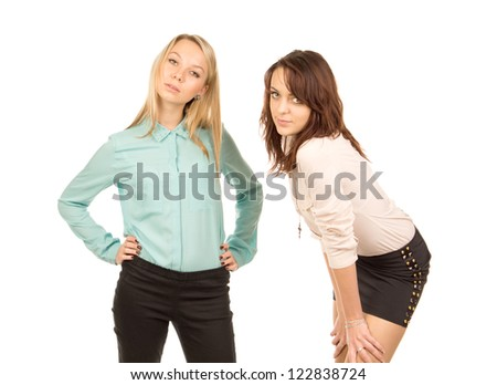 Two atrractive smiling young women standing having a chat, three quarter studio portrait on white