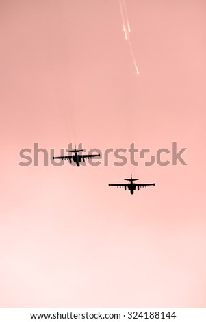 Two attack planes shooting decoy flares after the air strike on sunset - stock photo