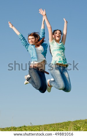 Two attractive brunettes in jeans jumping outdoors
