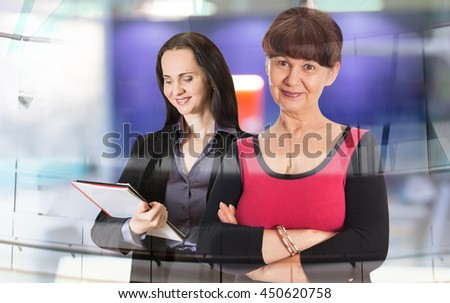 Two attractive business woman portrait in office agains of glass reflection - stock photo