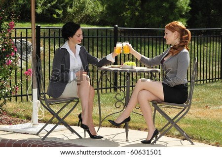 two attractive business women enjoying a lunch break together - stock photo