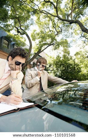 Two attractive businessmen meeting in a tree lined street, making calls and taking notes. - stock photo