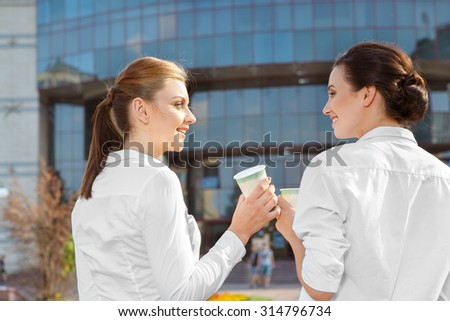 Two attractive businesswoman having a coffeebreak outdoors - stock photo