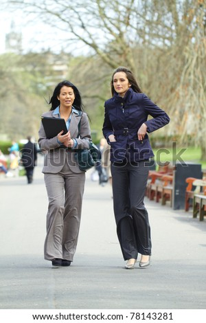 two attractive businesswoman walk in the park, both wear shirt and suit, elegant look, outdoor shoot - stock photo