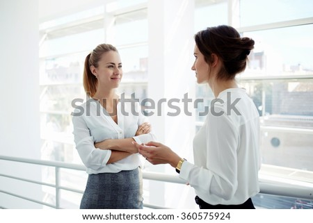 Two attractive businesswomen met in the office interior and stopped to talking about meeting with clients, female entrepreneurs dressed in corporate clothing having conversation during work break - stock photo